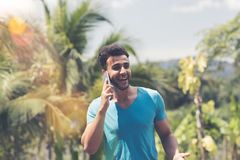 Latin Man Making Phone Call Over Tropical Forest And Blue Sky Background Happy Smiling Mix Race Guy Stock Image