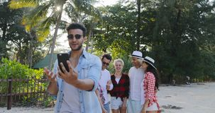 Latin Man Making Video Call Using Cell Smart Phone People Group Talking In Tropical Palm Tree Park. Slow Motion 60 stock video