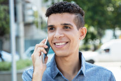 Latin man at phone in city Stock Photography