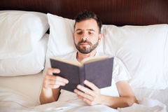 Latin man reading a book in the morning. Portrait of a handsome young Latin man reading a book in his bed, early in the morning Royalty Free Stock Image