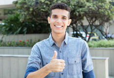 Latin man showing thumb in the city Stock Photo