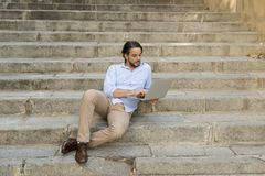 Latin man sitting on city staircase working with laptop computer looking satisfied and confident. Young attractive latin man sitting on city staircase working Royalty Free Stock Photography