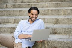 Latin man sitting on city staircase working with laptop computer looking satisfied and confident. Young attractive latin man sitting on city staircase working Stock Photos