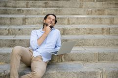 Latin man sitting on city staircase working with laptop computer looking satisfied and confident. Young attractive latin man sitting on city staircase working Royalty Free Stock Images