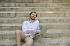 Latin man sitting on city staircase working with laptop computer looking satisfied and confident. Young attractive latin man sitting on city staircase working Royalty Free Stock Photo