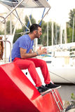 Latin man sitting on deck of red yacht at seaport Stock Photography