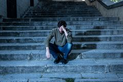 Depressed man sitting out side on steps feeling tired and sad. Latin man stressed from work sitting on steps outside feeling anxiety in adult cause of Stock Images
