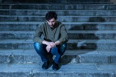 Depressed man sitting out side on steps feeling tired and sad. Latin man stressed from work sitting on steps outside feeling anxiety in adult cause of Stock Photos