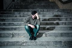 Depressed man sitting out side on steps feeling tired and sad. Latin man stressed from work sitting on steps outside feeling anxiety in adult cause of Royalty Free Stock Photography
