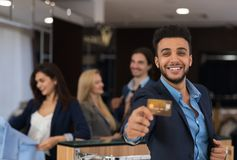 Latin Man In Suit Hold Credit Card Happy Smiling While Shopping In Elegant Menswear Store. Businessman Buy Clothes Royalty Free Stock Photo