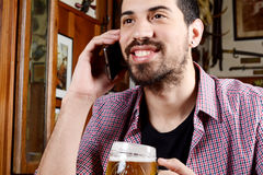 Latin man talking on the phone with glass of beer and snacks. Stock Images