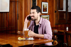Latin man talking on the phone with glass of beer and snacks. Royalty Free Stock Photos