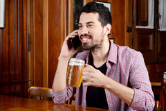 Latin man talking on the phone with glass of beer and snacks. Stock Photo