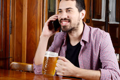 Latin man talking on the phone with glass of beer and snacks. Stock Image