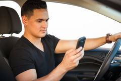 Latin man texting and driving Royalty Free Stock Photo