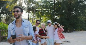 Latin Man Use Cell Smart Phone Chatting Online Over Cheerful People Group Dancing In Tropical Palm Tree Park. Slow Motion 60 stock video footage