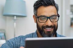 Latin man using digital tablet stock photo