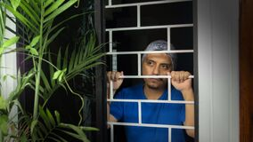 Free Latin Man With Blue Shirt Locked In His House Looking Out Through The Window, Leaning Against Security Bars Royalty Free Stock Photo - 180300765