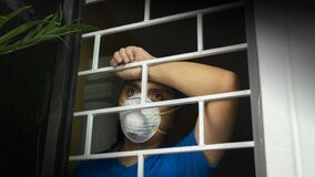 Free Latin Man With White Face Mask Inside His House Looking Out Through The Window, Leaning Against Security Bars Royalty Free Stock Photography - 180300637