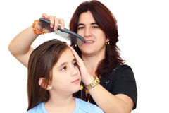 Latin mother combing her small daughter hair Stock Photo