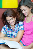 Latin mother and her daughter reading a boo Stock Photography