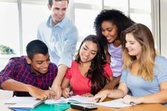 Latin- och indier- och afrikansk amerikanstudenter med läraren royaltyfria bilder