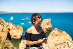 Latin pretty woman using smart phone  on the top of ocean rock. travel and active lifestyle concept Royalty Free Stock Images