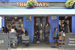 Latin Quarter, Galway, Ireland June 2017, The Quays Bar Main ent. Rance,  girls smoking and some people siting in the outside tables Stock Photo
