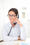 Latin receptionist conversing on the phone Royalty Free Stock Photo