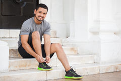 Latin runner tying his shoes outdoors. Handsome young Latin man tying his shoes and getting ready to workout and go for a run outdoors in the city Royalty Free Stock Photography
