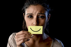 Latin sad depressed latin girl holding paper hiding her mouth behind fake drawn smile. Young beautiful Latin sad and depressed latin girl holding paper hiding Stock Photo