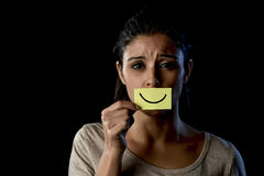 Latin sad depressed latin girl holding paper hiding her mouth behind fake drawn smile Stock Images