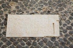 Latin Script on Stone Wall in Pompeii. An ancient stone plaque with latin script on stone wall in Pompeii royalty free stock image