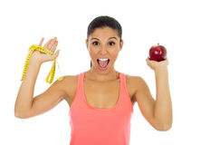 Latin sport woman in fitness clothes holding apple fruit and  m. Young beautiful latin sport woman in fitness clothes holding apple fruit and  measure tape Stock Photography