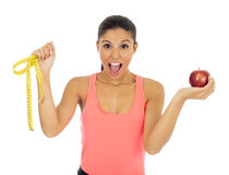 Latin sport woman in fitness clothes holding apple fruit and  m. Young beautiful latin sport woman in fitness clothes holding apple fruit and  measure tape Royalty Free Stock Image