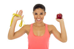 Latin sport woman in fitness clothes holding apple fruit and  measure tape smiling happy Stock Photography