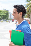 Latin student in the city looking sideways. With modern buildings in the background Royalty Free Stock Image