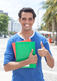 Latin student in the city showing thumb up. With modern buildings in the background Stock Image