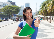 Latin student with long dark hair showing thumb in the city Royalty Free Stock Image