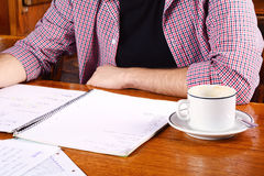 Latin student reading notes and drinking coffee. Close up of young latin student reading his notes and a cup of coffee at a cafe. Indoors Stock Images