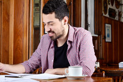 Latin student reading notes and drinking coffee. Portrait of young latin student reading his notes and drinking coffee at a cafe. Indoors Stock Photography