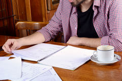 Latin student reading notes and drinking coffee. Portrait of young latin student reading his notes and a cup of coffee at a cafe. Indoors Stock Photo