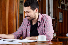 Latin student reading notes and drinking coffee. Portrait of young latin student reading his notes and a cup of coffee at a cafe. Indoors Stock Images