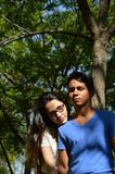 Latin teen couple with emotions, outdoors. Different emotions in a couple of Young teenagers in a green forest Royalty Free Stock Image