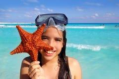Latin tourist girl holding starfish tropical beach stock photography