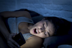 Latin woman on bed late at night texting using mobile phone yawning sleepy and tired Stock Photography