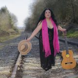 Latin woman with black dress walking on the train tracks with a pink shawl, a brown hat and a guitar. Beautiful latin woman with black dress walking on the train stock photography