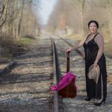 Latin woman with a black transparent dress standing on the train tracks with a pink shawl, a brown hat and a guitar. Beautiful latin woman with a black stock photos