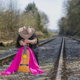 Latin woman in a black transparent dress that is on the train tracks behind a hat and a guitar. On an autumn day, observing how the rails are lost on the royalty free stock photography