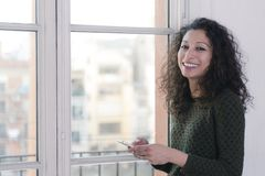 Woman with phone. Latin woman chating with her mobile phone next to a window at home Stock Photography